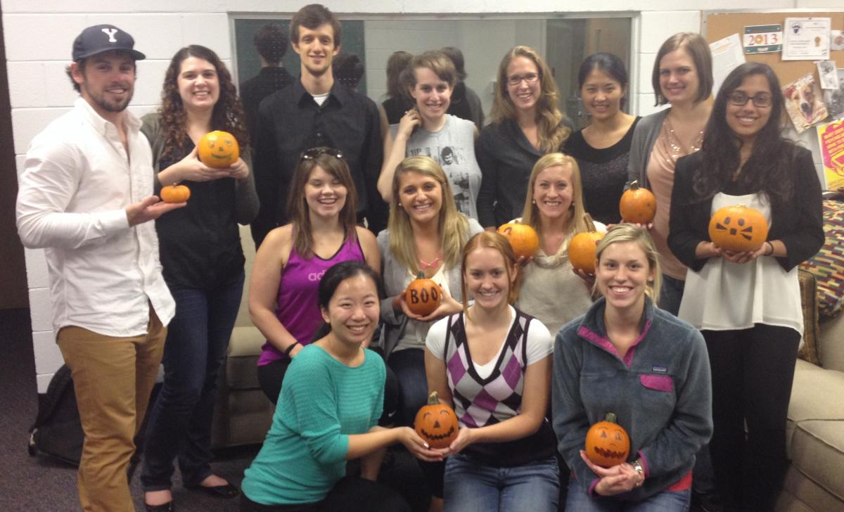 Graduate students show off their decorated pumpkins during the Halloween party