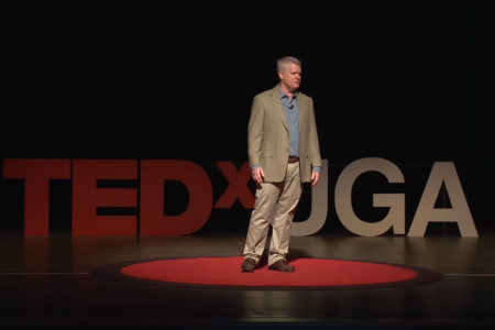 Keith Campbell stands on the UGA Tedx Stage and speaks about his research